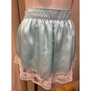 Teal color satin short with white laces.